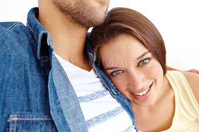 Buy stock photo Cropped close up portrait of an attractive young woman resting her head on her husband's chest