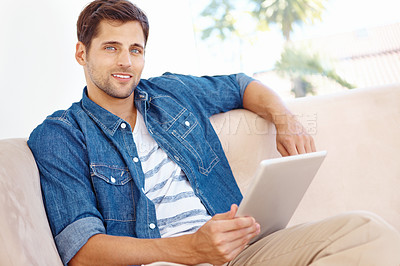 Buy stock photo Portrait of a handsome young man sitting on a sofa and using a digital tablet