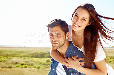 Buy stock photo Shot of a handsome young man giving his girlfriend a piggyback ride while going for a walk outside in a field