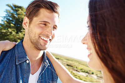 Buy stock photo Cropped shot of a handsome young man being hugged by his girlfriend outside in a field
