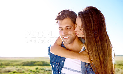 Buy stock photo Shot of a young and affectionate couple hugging while enjoying a sunny day out together