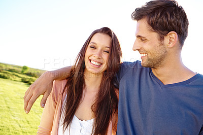 Buy stock photo Shot of a happy-looking young couple laughing while enjoying a sunny day outside