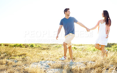 Buy stock photo Full length shot of a young man leading his girlfriend by the hand while walking in field