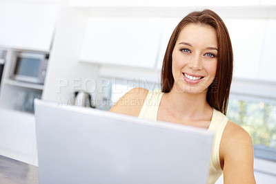 Buy stock photo Cute young woman using a laptop at home
