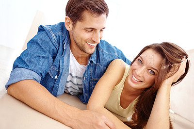 Buy stock photo Cute young couple lying together on the floor at home