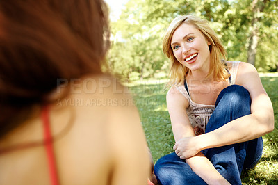 Buy stock photo Two beautiful friends sitting on the grass in a park and talking