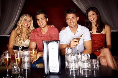 Buy stock photo Two gorgeous couples drinking in a night club