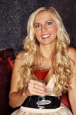 Buy stock photo Portrait of an attractive young blonde woman sitting on a sofa in a club and drinking a cocktail