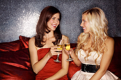 Buy stock photo Shot of two young woman toasting each other with champagne while sitting in a nightclub