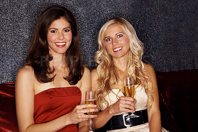 Buy stock photo Portrait of two attractive women drinking champagne while sitting in a nightclub