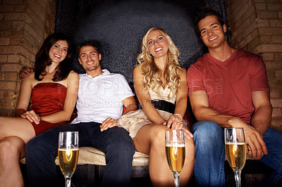 Buy stock photo Portrait of four good-looking young people sitting in a nightclub together and drinking champagne