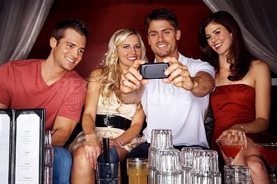 Buy stock photo Shot of a group of friends taking a self-portrait with a camera phone while in a nightclub