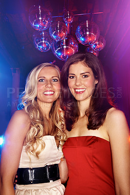 Buy stock photo Portrait of two attractive woman standing under disco balls in a nightclub