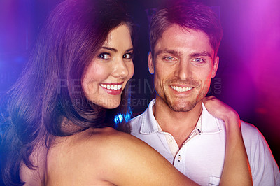 Buy stock photo Closeup portrait of a good looking young couple standing in a night club