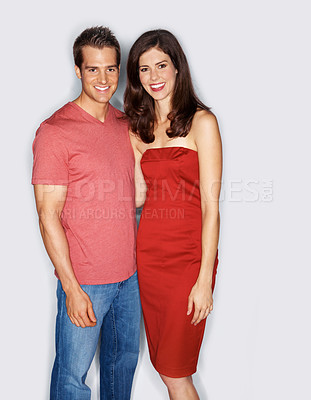 Buy stock photo Studio portrait of a good-looking young couple standing arm in arm