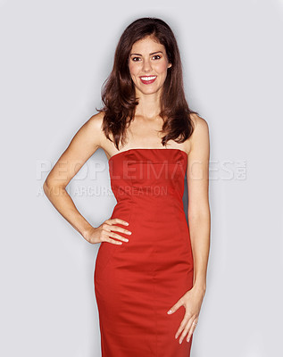 Buy stock photo Studio portrait of an attractive woman dressed in a red cocktail dress with her hand on her hip