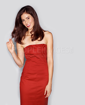 Buy stock photo Studio portrait of an attractive young woman dressed in a red cocktail dress