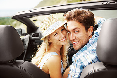 Buy stock photo Portrait of a young couple sitting in their car while on a roadtrip