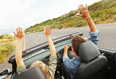 Buy stock photo Rearview of a young couple with their arms raised while on a roadtrip