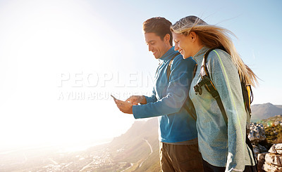 Buy stock photo Cute young couple using a mobile while out hiking together