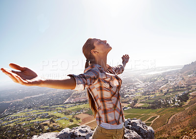 Buy stock photo Young woman feeling free while standing on a mountain top