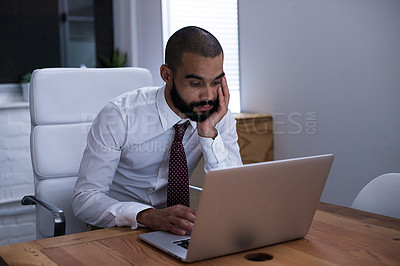 Buy stock photo Shot of a businessman working on his laptop late at night. Real life businesspeople shot on location. Since these locations are the real thing, and not shot in an