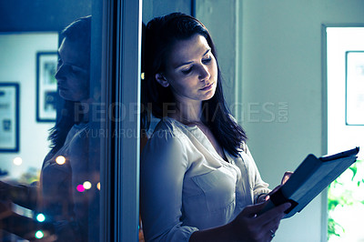 Buy stock photo Shot of a businesswoman using a digital tablet late at night. Real life businesspeople shot on location. Since these locations are the real thing, and not shot in an