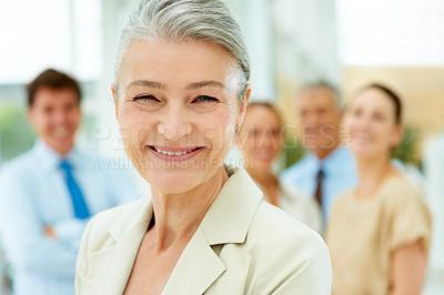 Buy stock photo Closeup portrait of successful senior businesswoman smiling with her colleagues in background