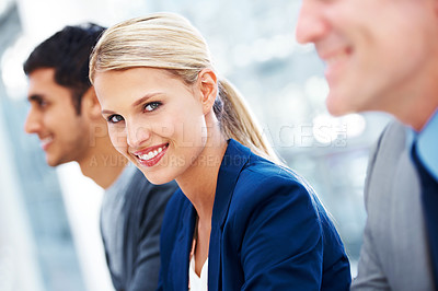 Buy stock photo Portrait of a gorgeous young businesswoman sitting with her colleagues in the office