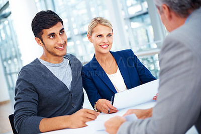 Buy stock photo Three businesspeople discussing documentation together