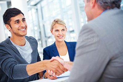 Buy stock photo Two businessmen shaking hands in the office with a female colleague looking on