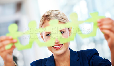 Buy stock photo A young businesswoman holding concertina-cut paper men