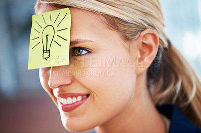Buy stock photo A gorgeous young woman with a sticky note with a picture of a lightbulb pasted to her head