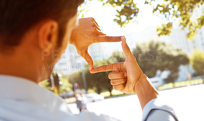Buy stock photo A businessman making a frame with his fingers outside
