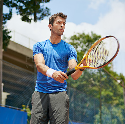 Buy stock photo Shot of a young tennis player ready serve