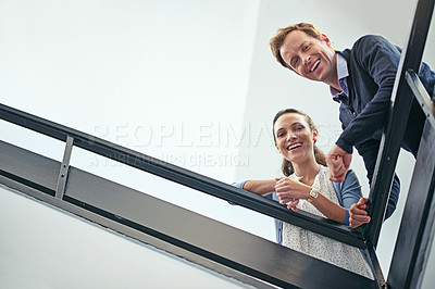 Buy stock photo Low angle portrait of two coworkers leaning on a stairwell bannister