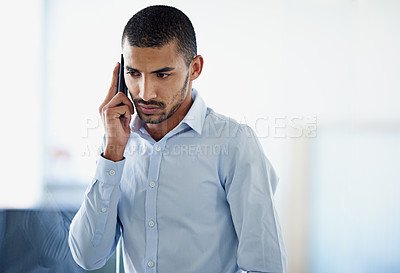 Buy stock photo Cropped shot of a handsome young businessman using in cellphone in the office