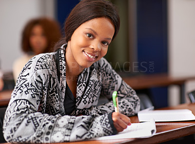 Buy stock photo Portrait shot of a happy female student sitting at her desk