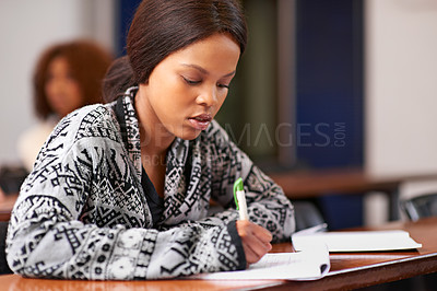 Buy stock photo Cropped shot of a student working diligently at her desk in class
