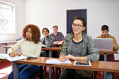 Buy stock photo Shot of a university students paying attention in class
