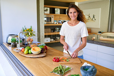 Buy stock photo Shot of an attractive young woman chopping vegetables in a kitchen