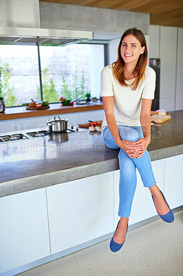 Buy stock photo Shot of an attractive young woman sitting on her kitchen counter