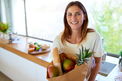 Buy stock photo An attractive woman holding a bag of groceries in the kitchen