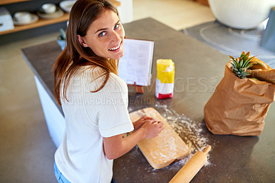 Buy stock photo Portrait of a young woman kneading dough in her kitchen