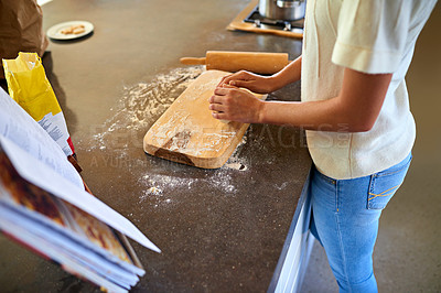 Buy stock photo Cropped shot of a young woman kneading dough in her kitchen