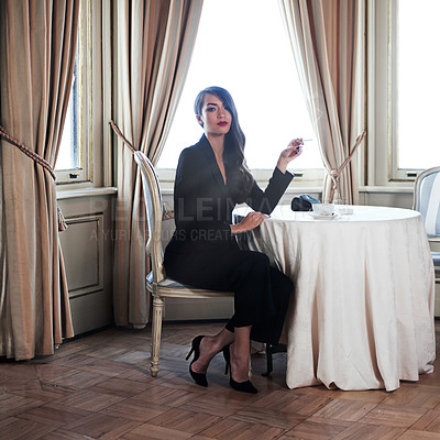Buy stock photo Shot of a woman smoking a cigarette in a luxurious setting wearing classicly elegant attire