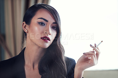 Buy stock photo Shot of an attractive and elegant young woman smoking