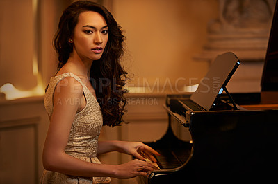 Buy stock photo Shot of a beautiful young woman playing the piano in an elegant room