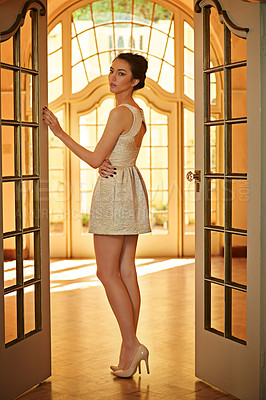 Buy stock photo A beautiful and elegantly dressed young woman standing  in a doorway