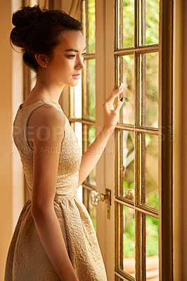 Buy stock photo Shot of an elegant young woman standing by a window